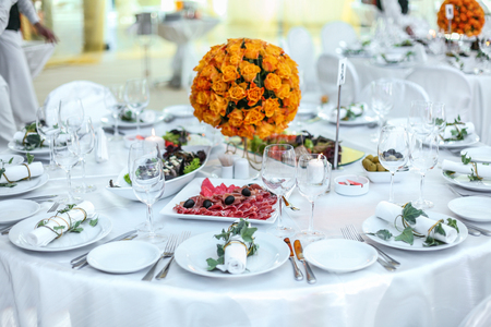 Holiday table setting decorated with flowers and candles. Foto de archivo