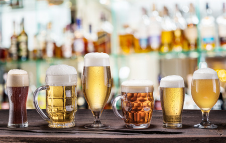 Cold mugs and glasses of beer on the old wooden table. Stock Photo
