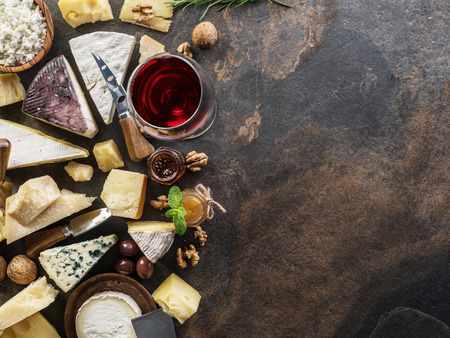 Cheese platter with organic cheeses, fruits, nuts and wine on stone background. Top view. Tasty cheese starter. 写真素材 - 118731947
