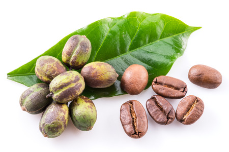Green coffee beans, roasted beans and fresh coffee leaves on white background. Macro. Stock fotó