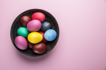 Colorful Easter eggs as an attribute of Easter celebration on the plate. Top view.