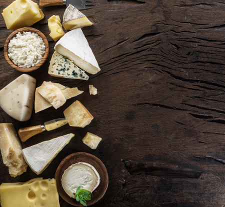 Assortment of different cheese types on old wooden background. Top view.