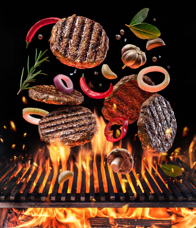 Beef milled meat on hamburger with vegetables and spices fly over the flaming grill barbecue fire. Concept of flying food.