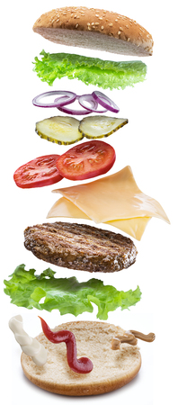 Hamburger ingredients falling down one by one to create a perfect meal. Colorful conceptual picture of burger cooking. Clipping path. Stock fotó