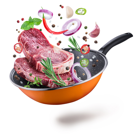 Flying meat steaks and spices over a frying pan. File contains clipping path. Flying motion effect.