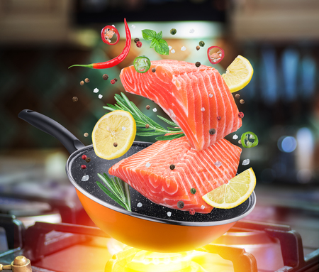 Flying salmon steak and spices falling into a frying pan. Flying motion effect of cooking process. Gas-stove at the background. Archivio Fotografico