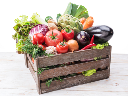 Fresh multi-colored vegetables in wooden crate. White background. Imagens