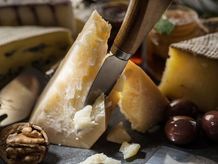Piece of Parmesan cheese and assortment of different cheeses at the background. Archivio Fotografico