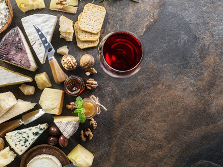 Cheese platter with organic cheeses, fruits, nuts and wine on stone background. Top view. Tasty cheese starter. Foto de archivo