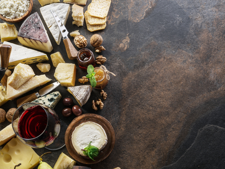 Cheese platter with organic cheeses, fruits, nuts and wine on stone background. Top view. Tasty cheese starter. 写真素材 - 119387647