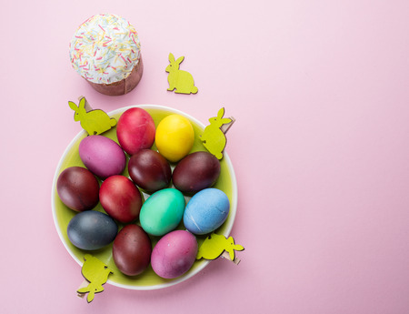 Colorful Easter eggs and Easter bread attributes of Easter celebration. Pink background.