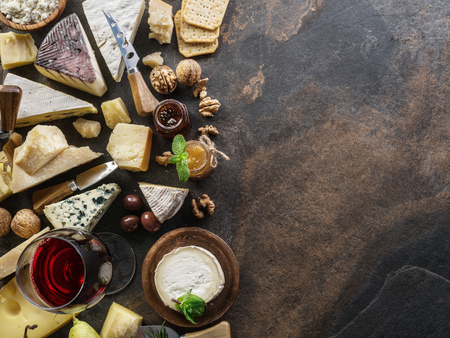 Cheese platter with organic cheeses, fruits, nuts and wine on stone background. Top view. Tasty cheese starter. 写真素材 - 119387664