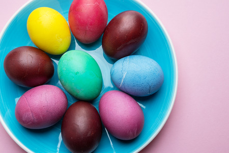Colorful Easter eggs as an attribute of Easter celebration. Pink background. Stock Photo