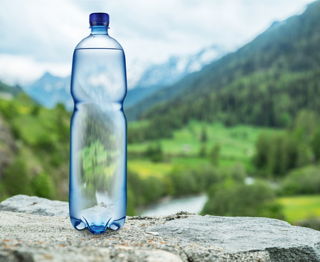 Bottle of water on the stone. Blurred snow mountains tops and green forests at the background, as a symbol of freshness and purity. Stock Photo