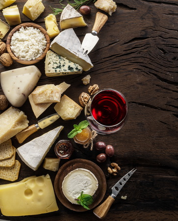 Cheese platter with organic cheeses, fruits, nuts and wine on wooden background. Top view. Tasty cheese starter. 写真素材 - 119389329