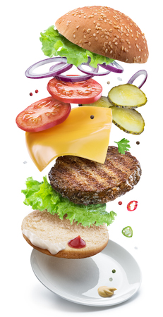 Hamburger ingredients falling down one by one to create a perfect meal. Colorful conceptual picture of burger cooking. Clipping path. Imagens