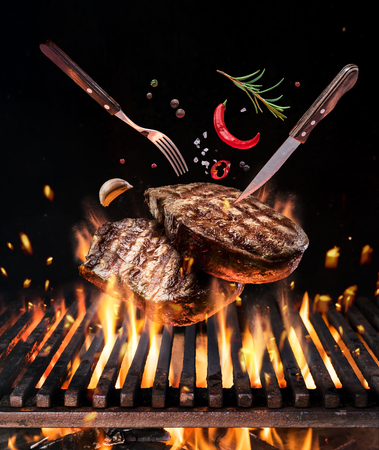 Raw beef steaks with vegetables and spices fly over the blazing grill barbecue fire. Concept of flying food.