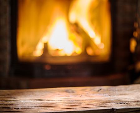 Stary drewniany stół i kominek z ciepłym ogniem w tle.
