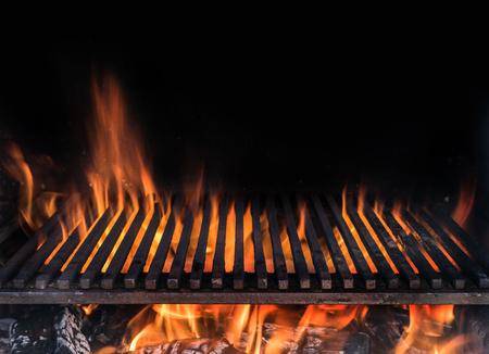 Griglia vuota e lingue di fiamma di fuoco. Priorità bassa di notte del barbecue.