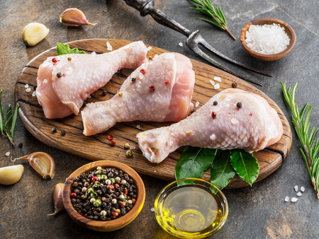 Chicken legs with spices and salt  ready for cooking on cutting board. Standard-Bild - 121242282