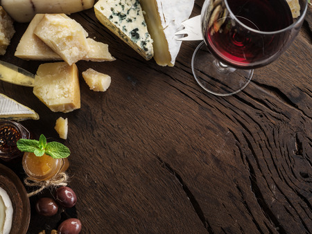 Cheese platter with organic cheeses, fruits, nuts and wine on wooden 写真素材 - 121242352