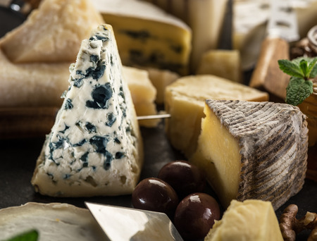 Segment of blue mould cheese with olives and range of cheeses 写真素材 - 121243333
