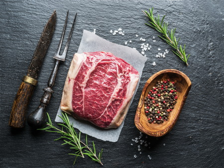 The top blade steak or beef steak on the graphite board with herbs and spices.