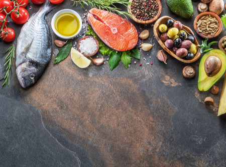 Raw dorado fish and salmon steak with spices and vegetables on the graphite board. Top view.