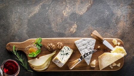 Cheese platter with organic cheeses, fruits, nuts and wine on stone 写真素材