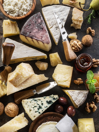 Assortment of different cheese types on stone background. Top view.