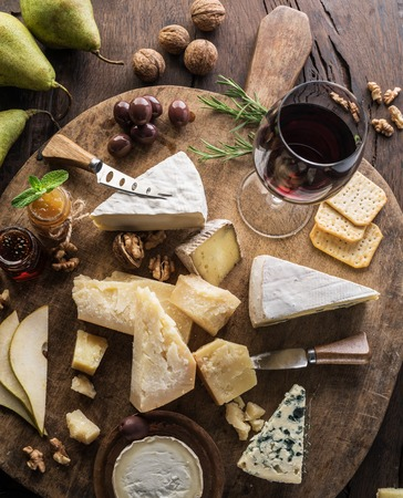 Cheese platter with organic cheeses, fruits, nuts and wine on wooden background. Top view. Tasty cheese starter. Stock Photo