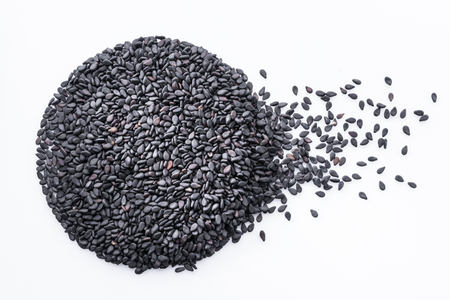 Black sesame seeds arranged in shape of circle on white background. Top view.