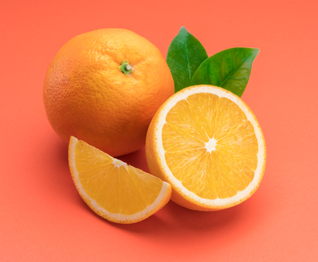 Orange fruit with orange slices and leaves isolated on orange background.