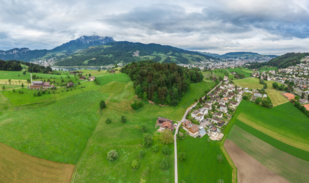 Village Horn, Mount Pilatus, Switzerland, May 13, 2018. Green spring fields and cloudy sky. 免版税图像