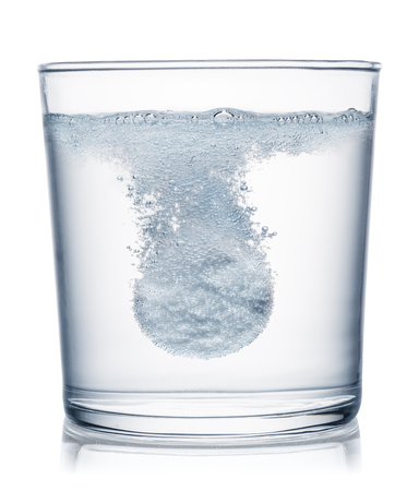Effervescent tablet dissolving in a glass of water. File contains clipping path.