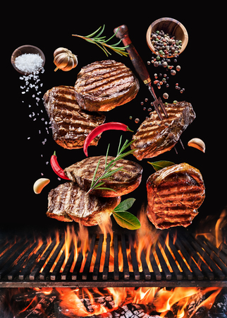 Grilled beef steaks with vegetables and spices fly over the blazing grill barbecue fire. Concept of flying food. 版權商用圖片