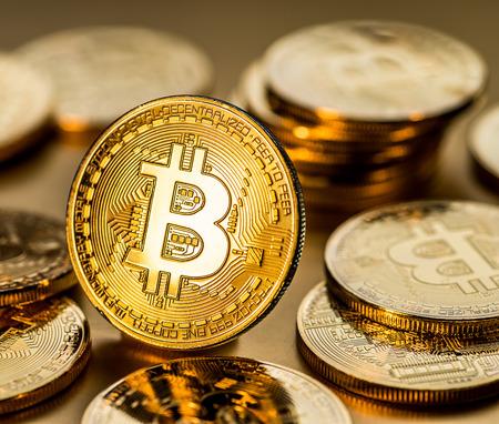Shiny physical bitcoins on golden background. Blockchain technology.