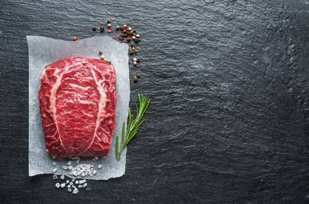 The top blade steak or beef steak on the graphite board with herbs and spices. Banque d'images