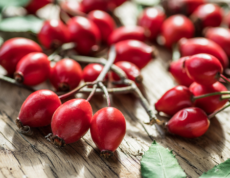 Ripe rose-hips or wild rose berries on a wooden Stock Photo