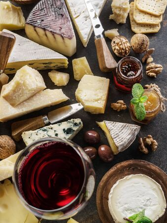 Cheese platter with organic cheeses, fruits, nuts and wine on stone background. Top view. Tasty cheese starter. 写真素材