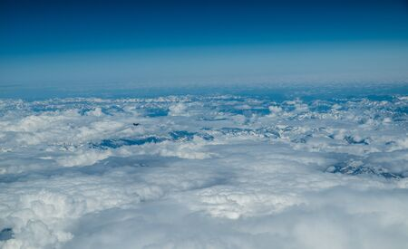 Small figure of an airplane. White heavy clouds in the blue sky. Panoramic cloudscape above the clouds.