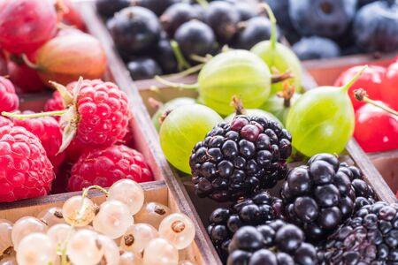 Wooden box with colorful berries. Close-up.