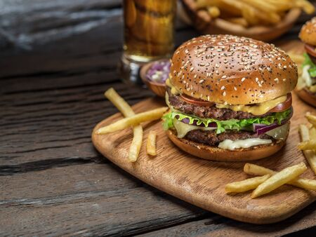Hamburger and French fries on the wooden tray.