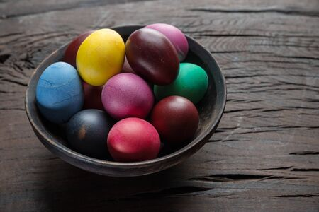 Colorful Easter eggs in bowl on wooden table.  Attribute of Easter celebration.