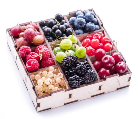 Colorful berries in wooden box on white background. Top view.