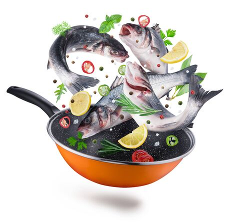 Flying seabass fishes and spices falling into a frying pan. Flying motion effect of cooking process. Stock Photo