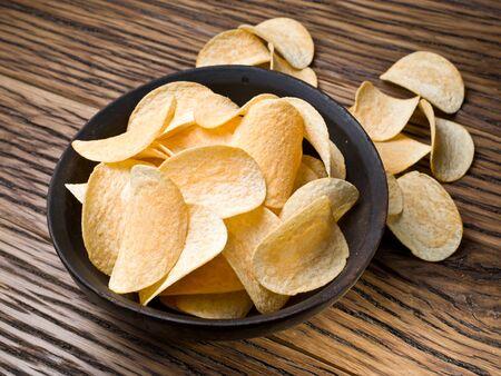 Potato chips on a wooden Фото со стока