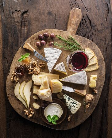 Cheese platter with organic cheeses, fruits, nuts and wine on wooden 写真素材