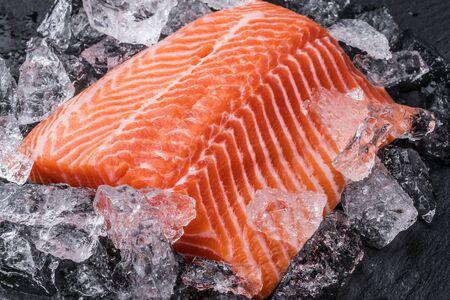 Filetto di salmone fresco su ghiaccio su tagliere nero. Avvicinamento.