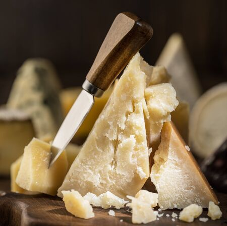 Piece of Parmesan cheese  on the wooden board.